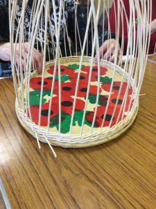Part weaved basket with poppy decoration on base